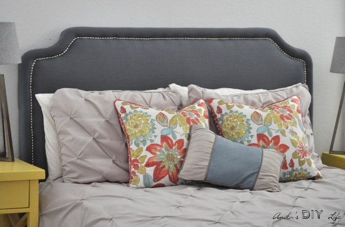 DIY upholstered headboard with nailhead trim and colorful pillows