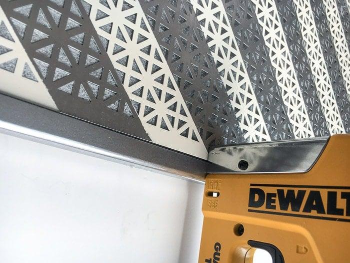 Attaching the metal sheet to corkboard for a DIY Jewelry Organizer using a staple gun