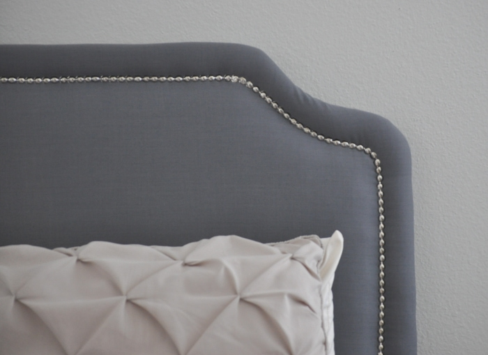 Make an upholstered bed with nailhead trim with this step by step tutorial to build the frame and upholster it!