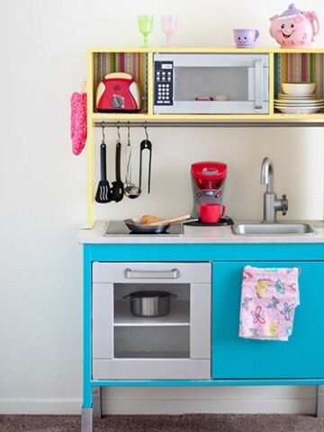 This Ikea Duktig Kitchen hack takes the plain Ikea kitchen and transforms it into a fun and colorful kids play kitchen with just a bit of paint and paper!