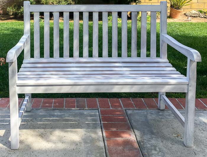 Outdoor bench with one coat of primer in backyard