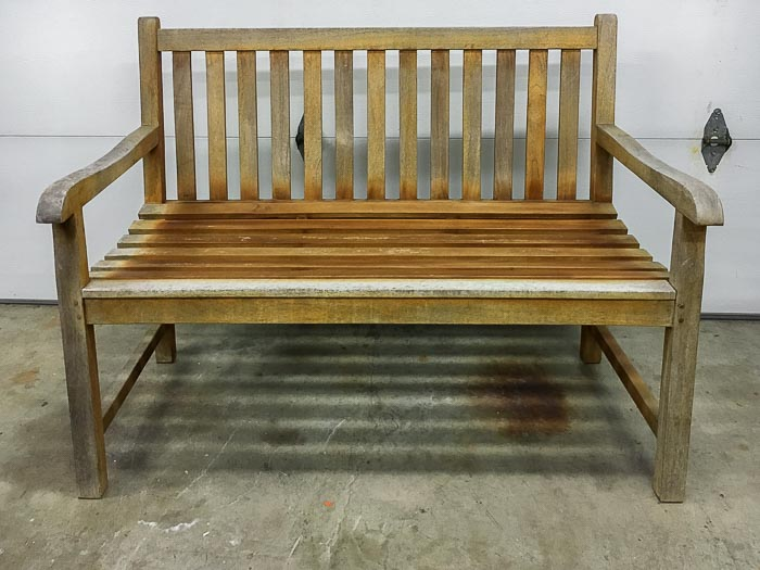 Old beaten up wooden patio bench in garage