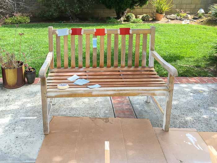 Old outdoor bench with paint chips taped in backyard