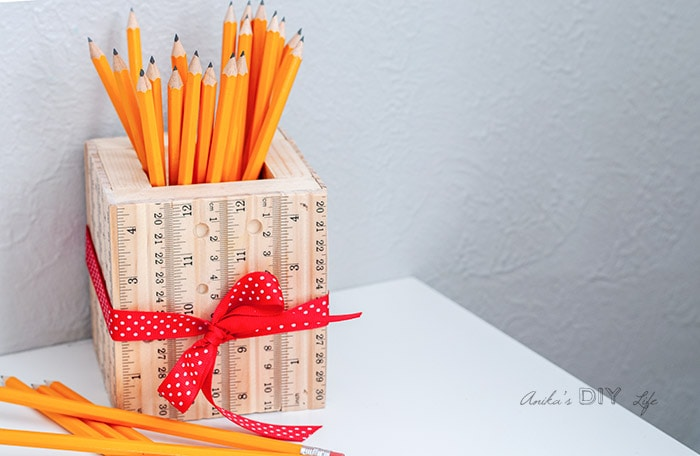 DIY pencil holder made from scrap wood and rulers on table with yellow pencils