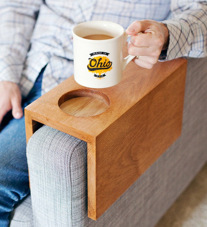 wooden couch sleeve with man holding mug