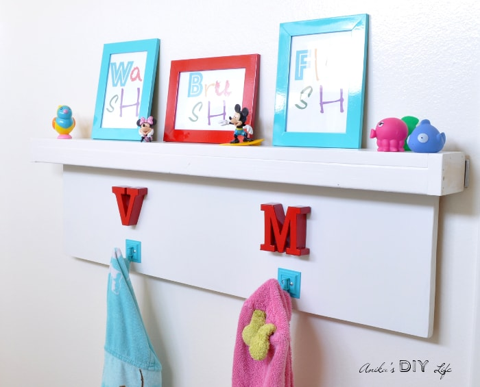 DIY Towel hooks and floating shelf for kids rental bathroom makeover.