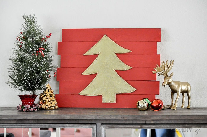 DIY Christmas wall decor with green Christmas tree on red plaque on console table with other Christmas decorations.