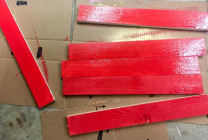 1x3 boards painted red and waiting to dry