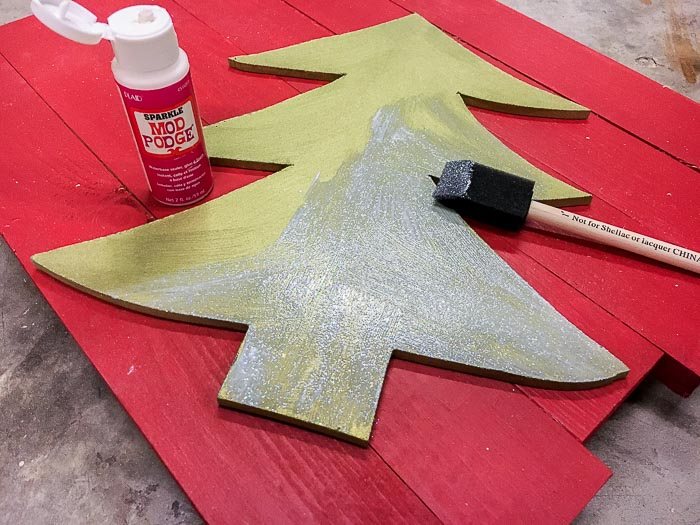 green painted Christmas tree cut out with sparkle mod podge being added.