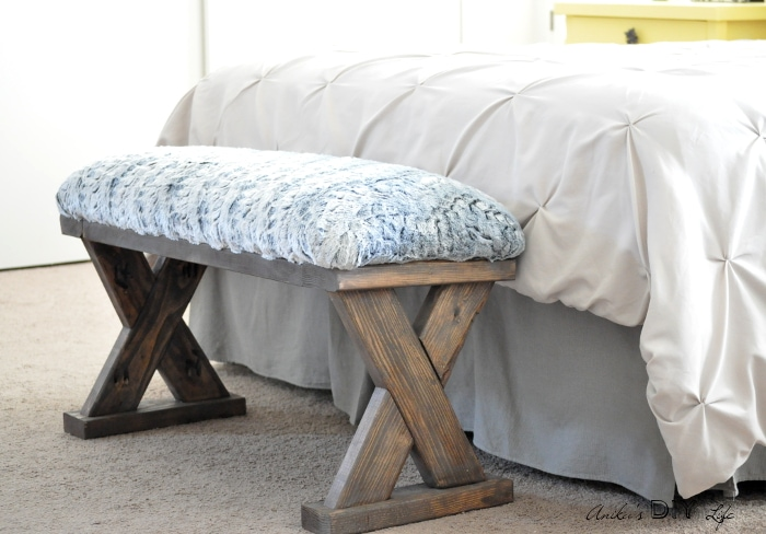 DIY upholstered X-leg bench made with 2x4 boards as an end of the bed bench.