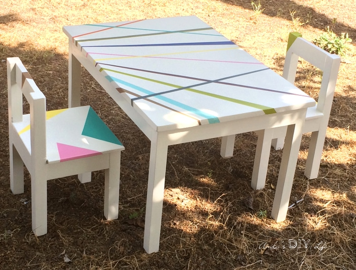 White DIY kids table and chair with colorful stripes in back yard