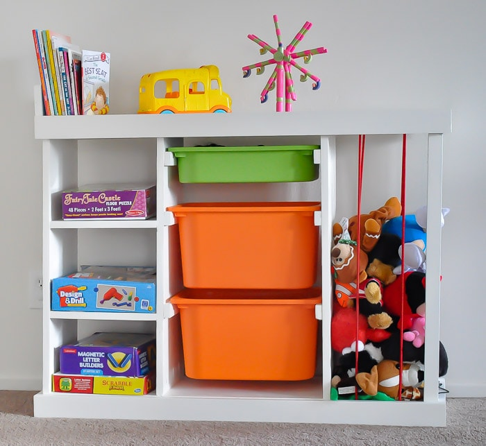 DIY TOy organizer with books, board games, bins, and soft toys