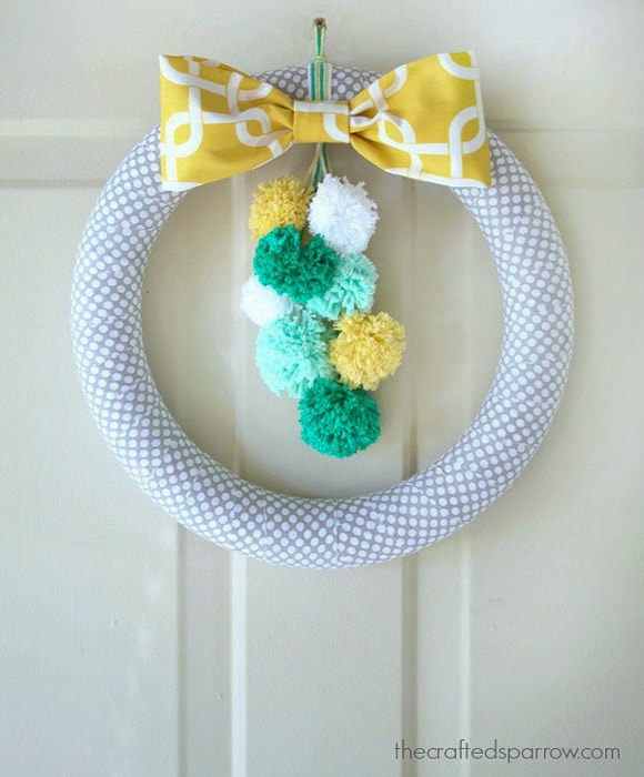 foam wreath wrapped in fabric with colorful pom poms
