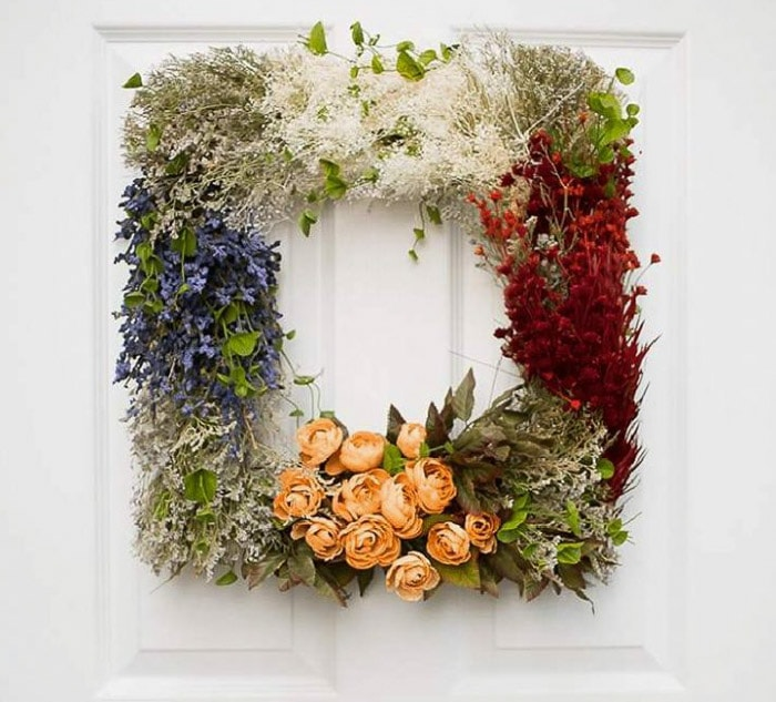 square wreath made with faux wildflowers and roses