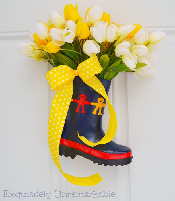 rainboot filled with faux flowers and a yellow ribbon