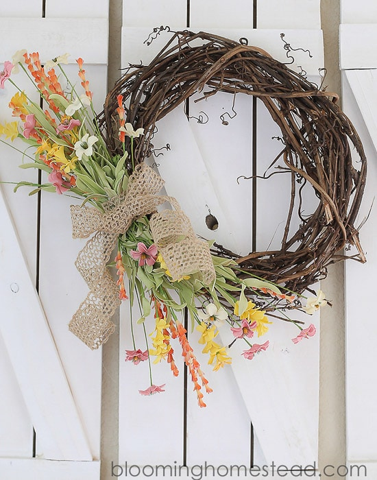 grapevine wreath with burlap bow and faux colorful flowers