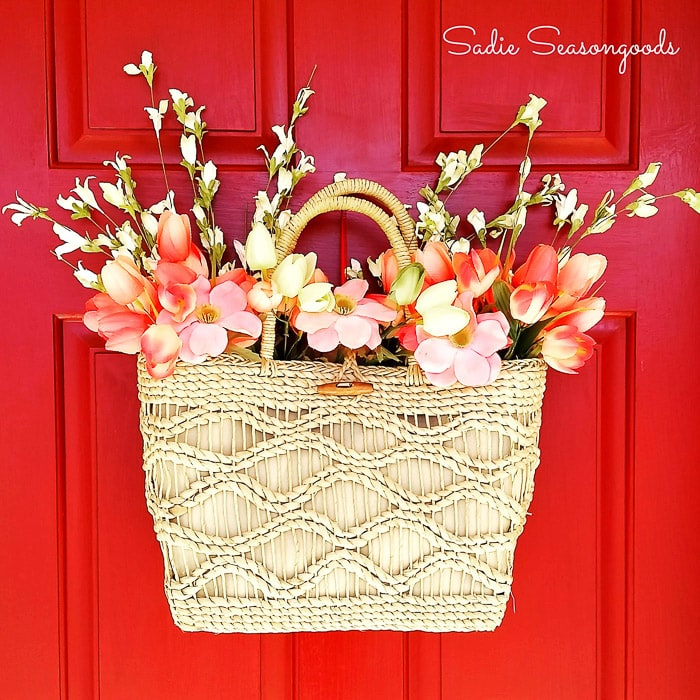 Basket with colorful flowers on the front door