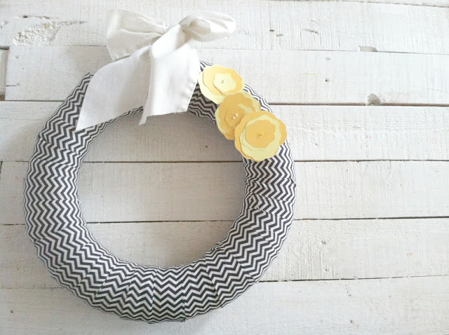 Foam wreath wrapped in zigzag fabric with yellow paper flowers and white bow