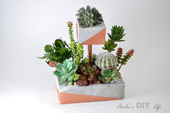 Tiered concrete planter with faux succulents in it