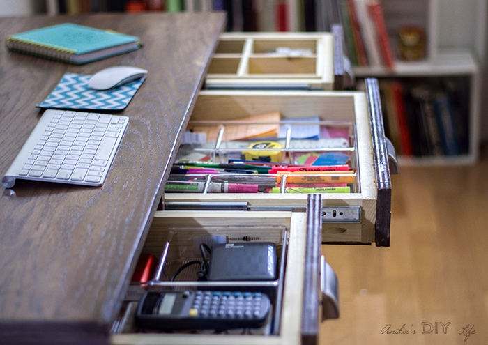 Drawers inside the desk with organized pens and markers