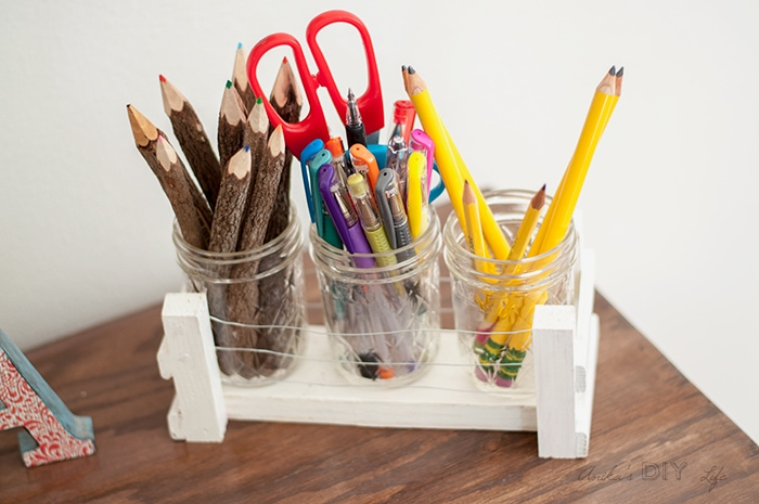 Mason jar with wood and wire holder on desk with pencils