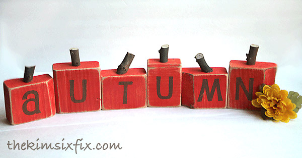 "wooden blocks painted red with letters stenciled to read ""autumn"""