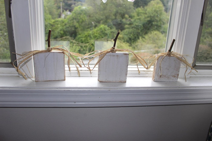 Small white scrap wood pumpkins on window