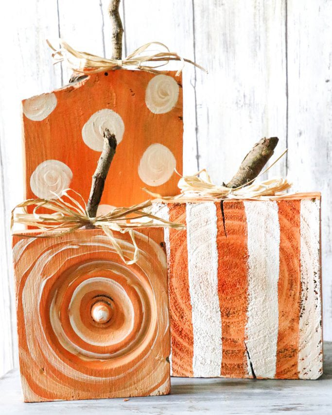 Rustic painted wood pumpkins in white and orange.