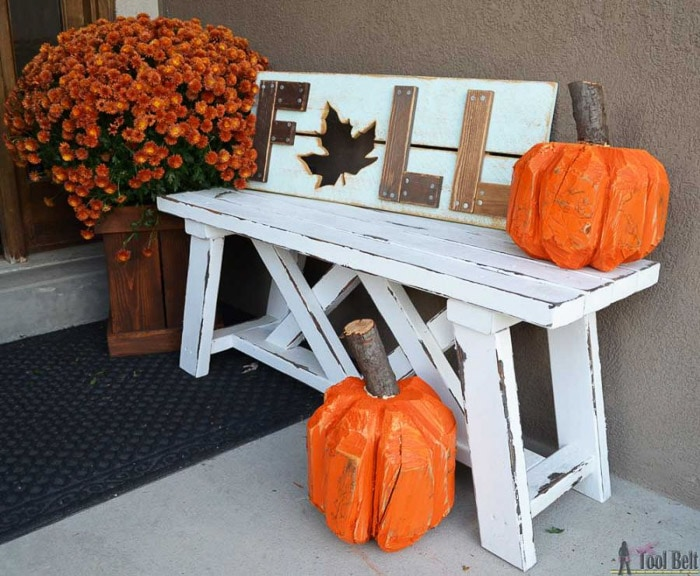 Carved stump turned pumpkin on an outdoor bench