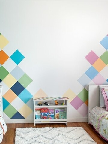 This colorful accent wall is perfect for kids room. Learn how to easily paint this DIY geometric accent wall in a couple of days and create the perfect feature wall.