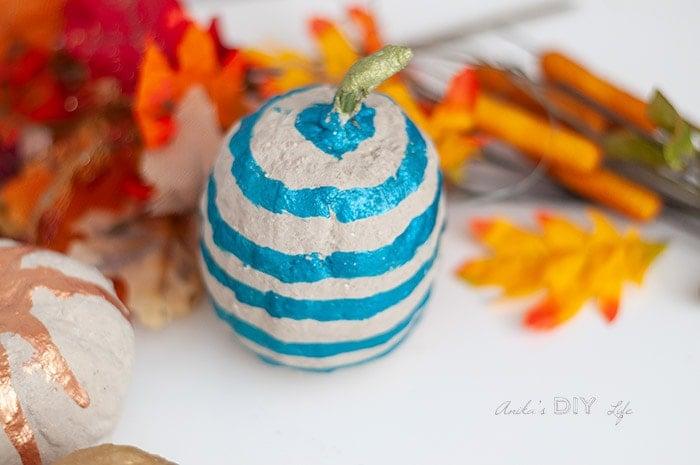 Close up of DIY cement pumpkin wit blue stripes