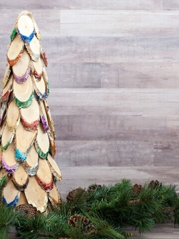 This colorful wood slice Christmas tree is the perfect DIY wooden Christmas decoration. Add lots of bright sparkle to your mantle or doorstep!