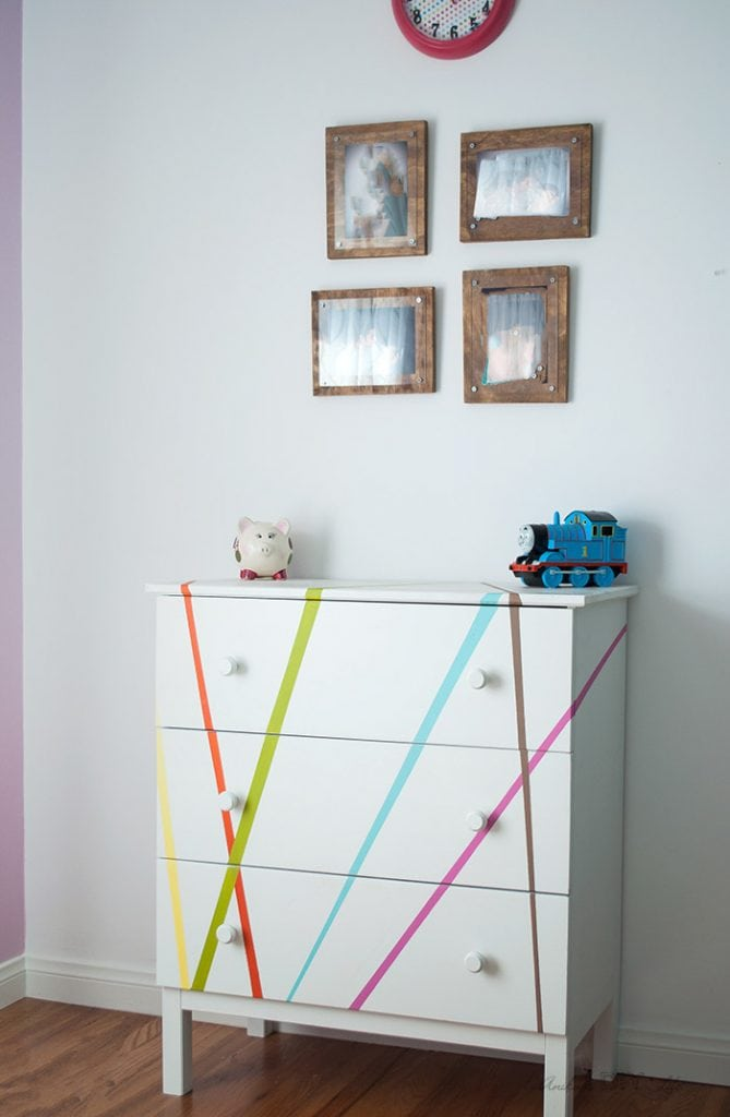 Colorful dresser in kids room with picture frames on top.
