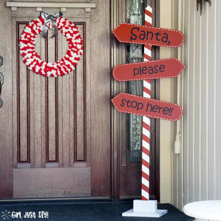 Red and white striped Santa Please Stop Here wood pole with directional arrows