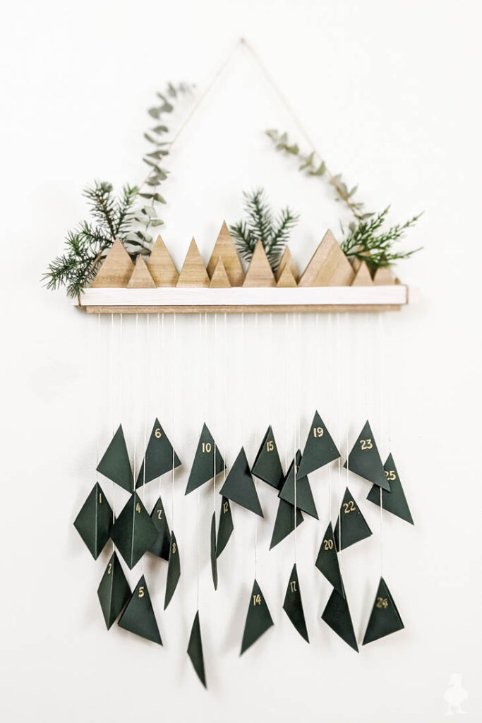 small wood triangle trees on shelf with hanging advent calendar hanging from it