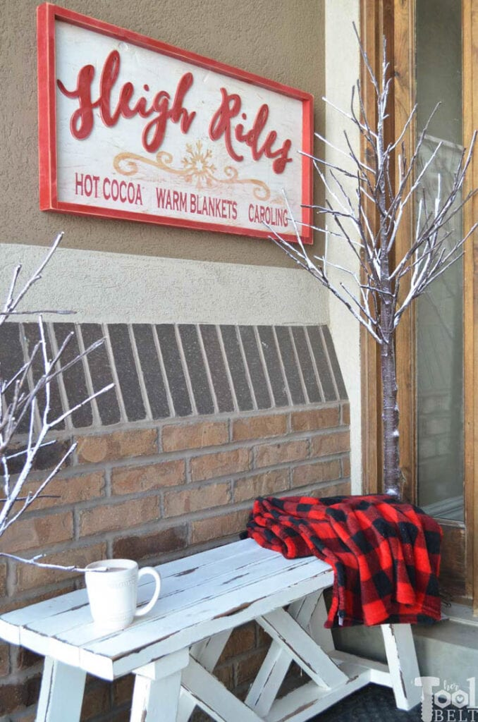 Wood sleigh ride sign hanging on porch