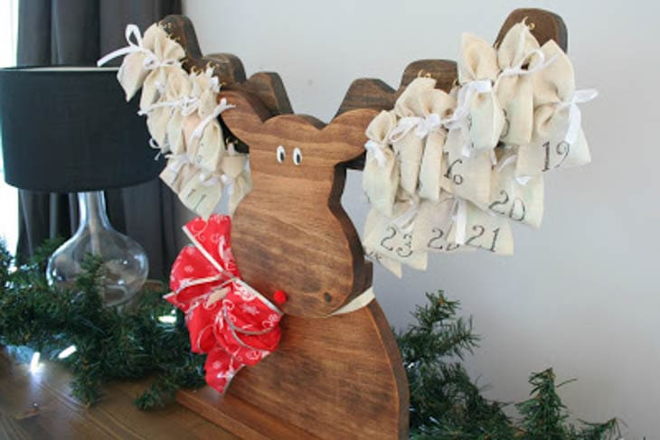 Wood moose advent calendar with day markers hanging on antlers