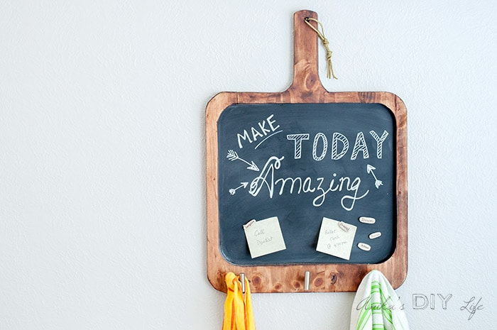 Magnetic chalkboard shaped like a cutting board on wall with note and towel hanging.