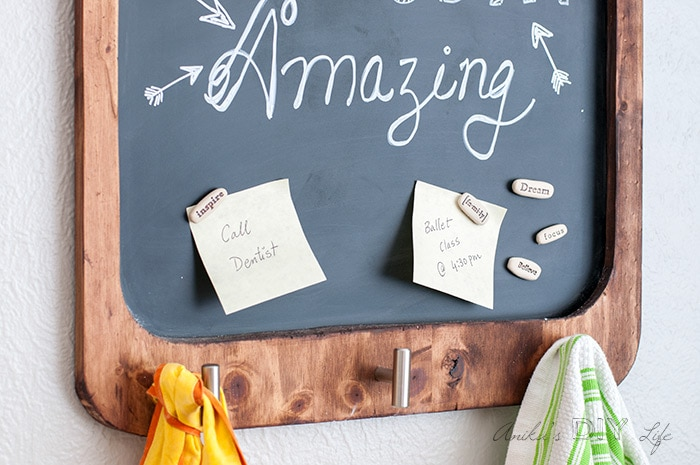Close up view of the magnetic chalkboard with doodle and rock magnets. Kitchen towel and apron hanging on the knobs