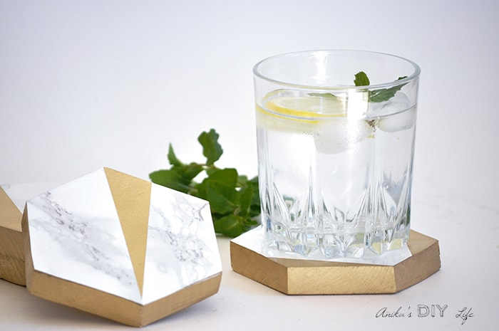 Gold and marble hexagonal coasters with a glass of water