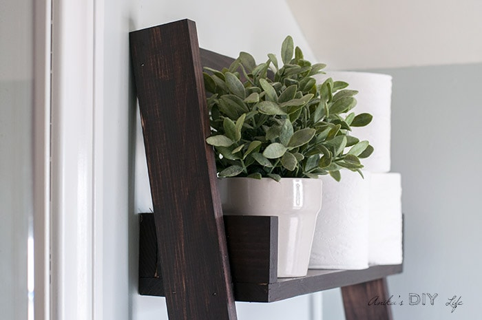 Flower pot with faux greenery on floating ladder shelf.