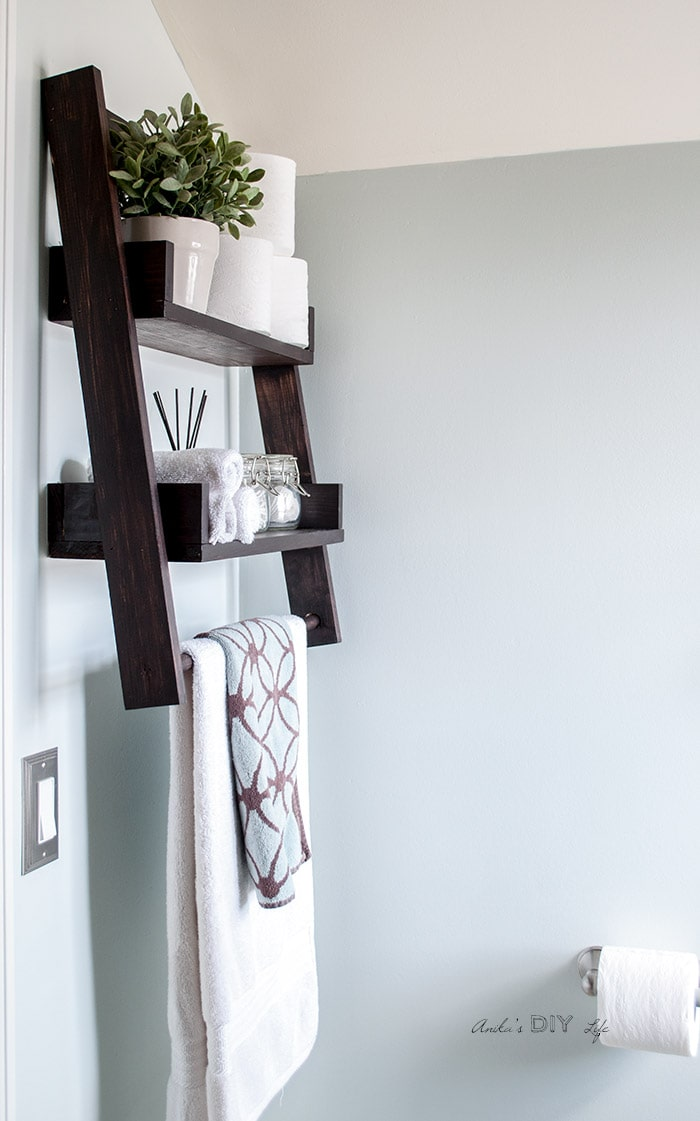 Floating ladder shelf mounted on bathroom wall with flower pot, towels and toileteries