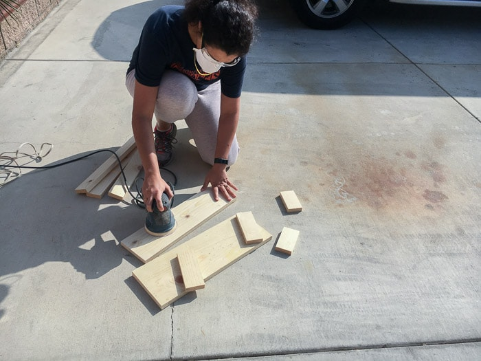 Sanding wood boards for DIY floating ladder shelf with orbital sander
