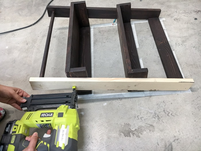 Attaching the side of the floating ladder shelf using glue and finish nails.