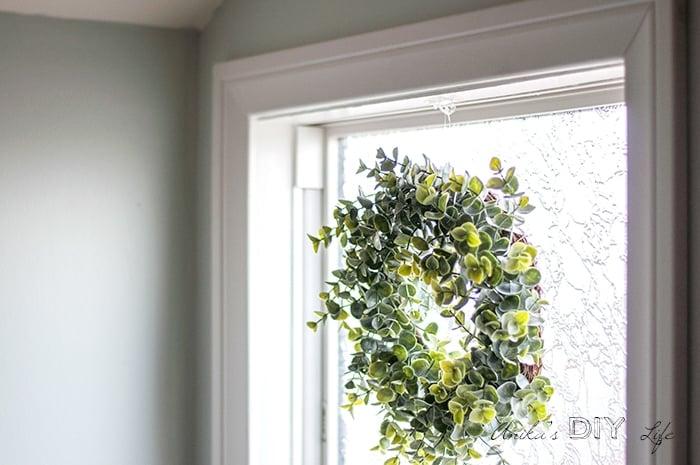 faux boxwood wreath form in bathroom window