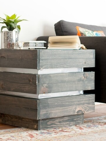 This DIY three tier end table is the perfect addition to any living space. It is chunky and rustic with a modern metallic touch.