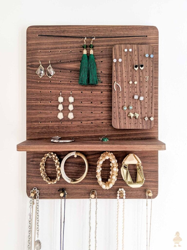 Wood wall hanging jewelry organizer with shelf with necklaces, earrings and bracelets