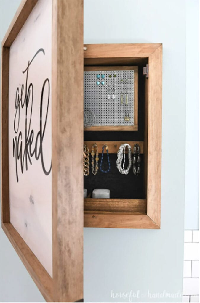 wooden jewelry organizer hanging on wall with door open