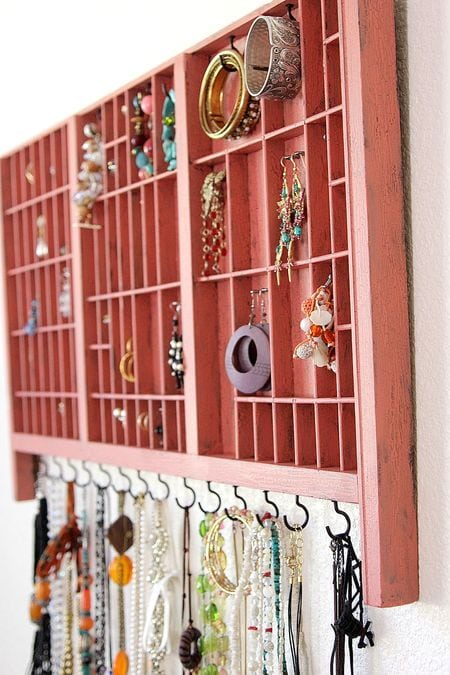 Hanging jewelry organizer painted salmon pink made from an old typeset tray