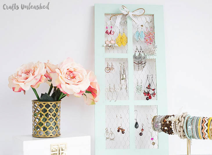 Upcycled window with chicken wire for hanging jewelry organization